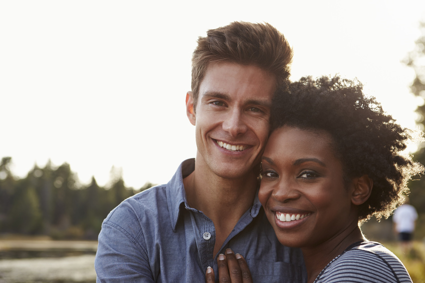 Mixed race couple in the countryside, looking to camera